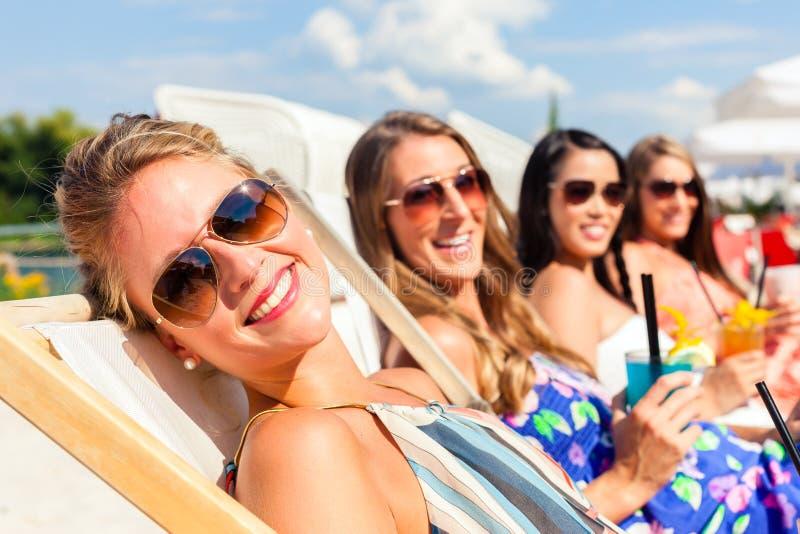 Amici che si abbronzano nella barra della spiaggia fotografia stock libera da diritti