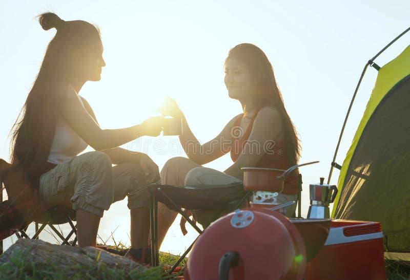 Amici che si accampano mangiando concetto dell'alimento, coppia asiatica che si accampa in loro tenda il giorno soleggiato, conce fotografia stock