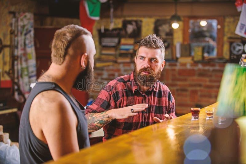 Amici che si rilassano nella barra o nel pub Conversazione ubriaca dei Soulmates Uomo barbuto brutale dei pantaloni a vita bassa  immagine stock