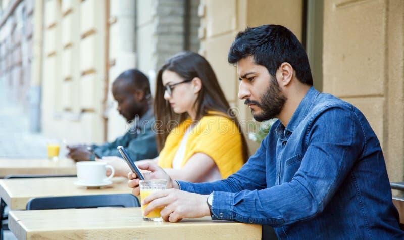 Amici che si siedono con gli Smartphones fotografia stock libera da diritti