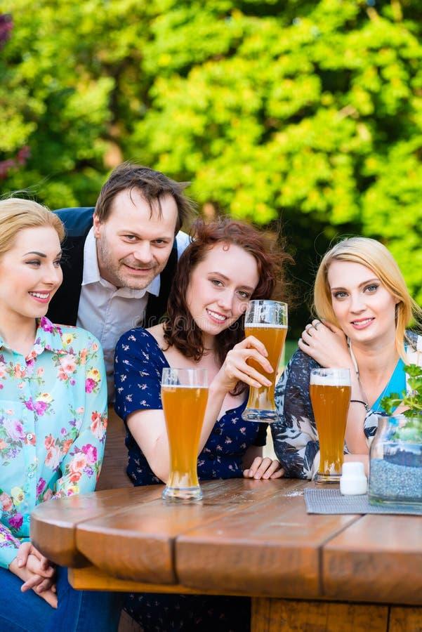 Amici che si siedono nel ristorante del giardino della birra immagini stock