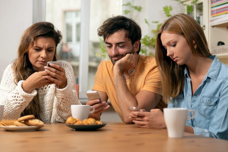 Amici che si siedono nella cucina e che guardano sui loro telefoni immagine stock libera da diritti