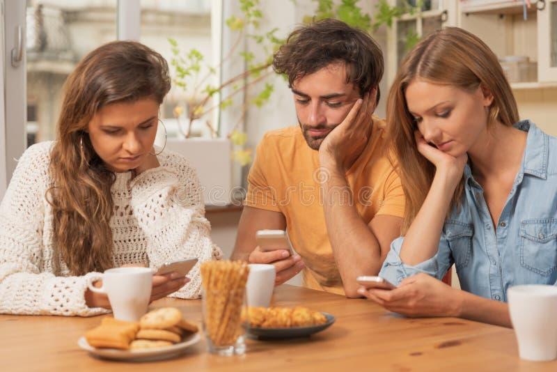 Amici che si siedono nella cucina e che guardano sui loro telefoni immagine stock