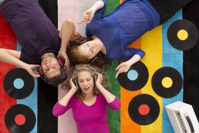 Amici che si trovano sul tappeto circondato dai vinili fotografia stock libera da diritti