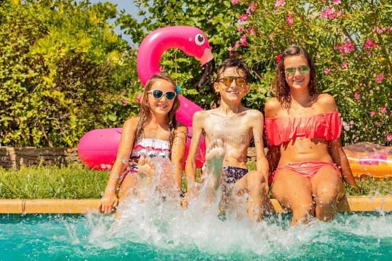 Amici che spruzzano acqua con le gambe nella piscina fotografie stock