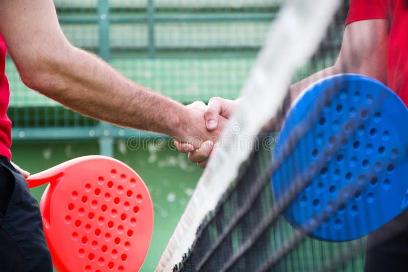 Amici che stringono le mani nelle paddle tennis immagini stock libere da diritti