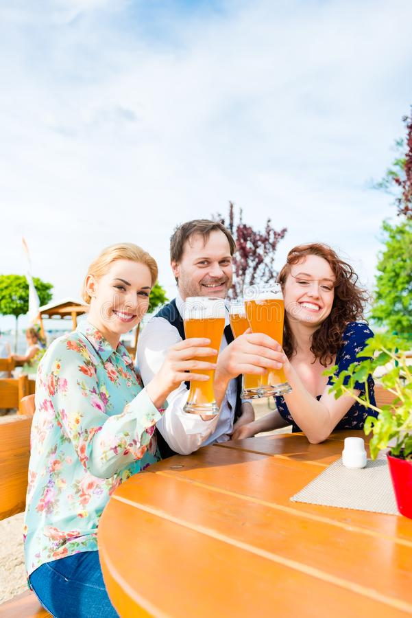 Amici che tostano con la birra nel ristorante del giardino immagini stock