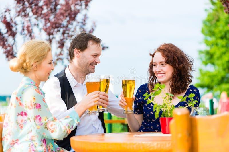 Amici che tostano con la birra nel ristorante del giardino fotografia stock