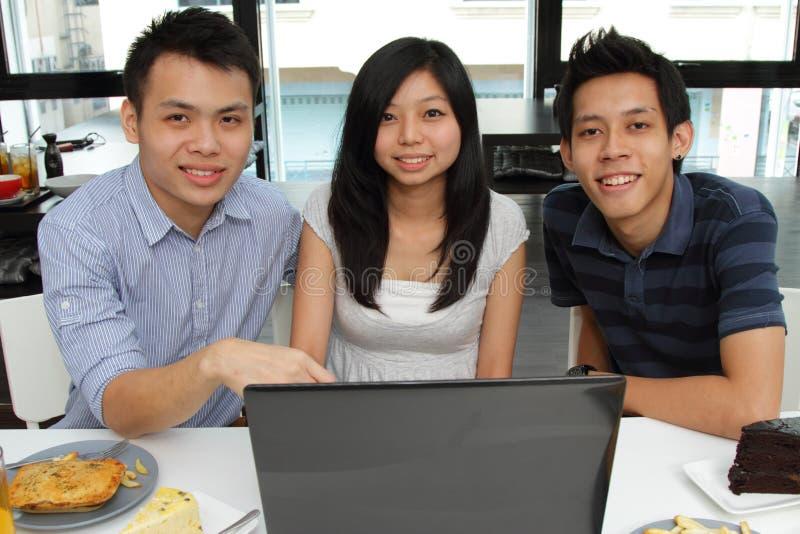 Amici che utilizzano un computer portatile in un caffè immagine stock libera da diritti