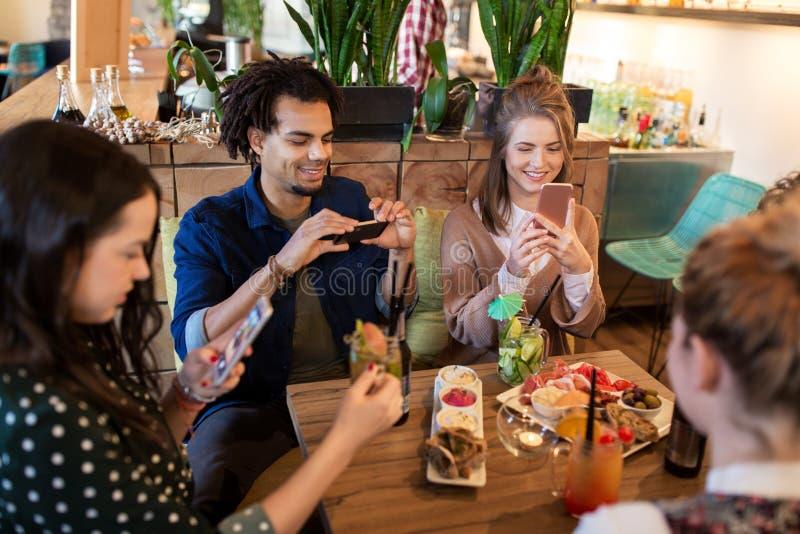 Amici con gli smartphones e l'alimento al ristorante immagini stock