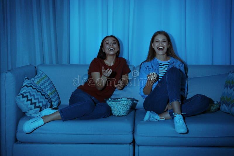 Amici con la ciotola di popcorn che guarda insieme TV sul sofà fotografia stock