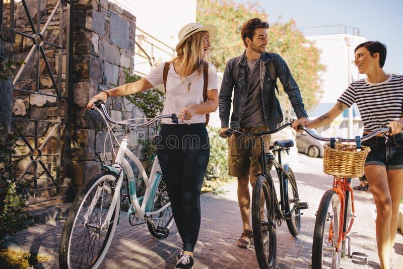 Amici con le bici che camminano all'aperto nella città immagine stock