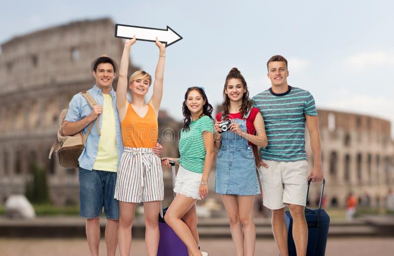 Amici con le borse di viaggio e freccia sopra il Colosseo immagine stock libera da diritti