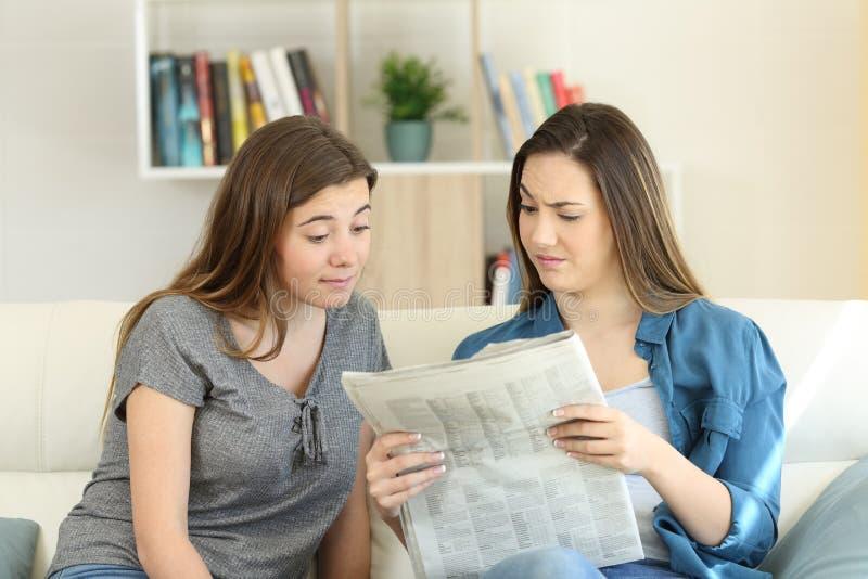 Amici confusi che leggono le notizie del giornale fotografie stock libere da diritti
