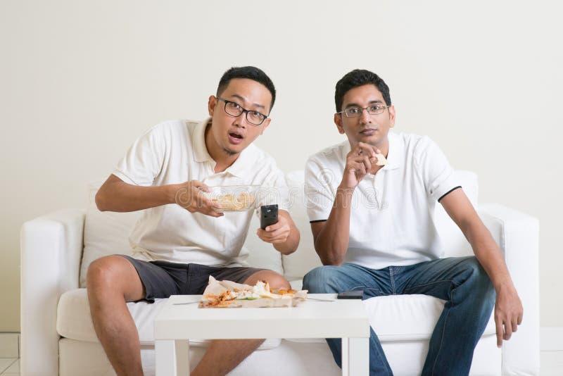 Amici degli uomini che guardano insieme la partita di sport sulla TV fotografia stock