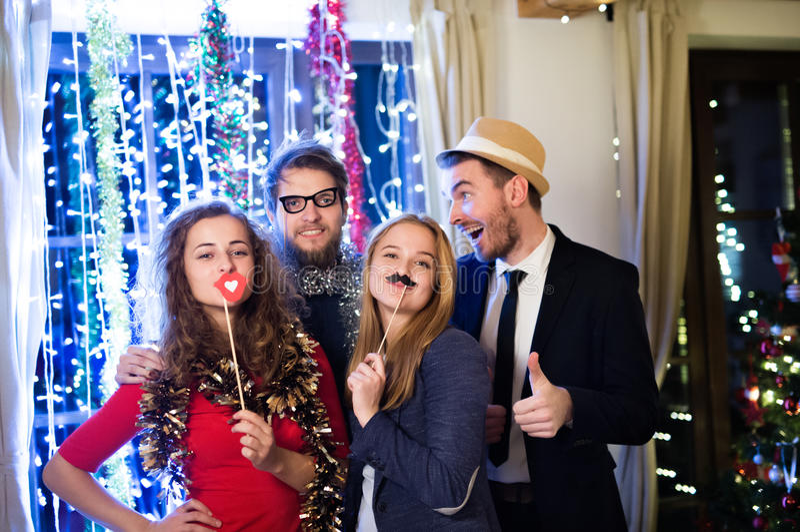 Amici dei pantaloni a vita bassa che celebrano insieme i nuovi anni EVE, photobooth p fotografie stock