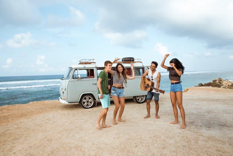 Amici dei pantaloni a vita bassa che godono del tempo alla spiaggia fotografia stock libera da diritti