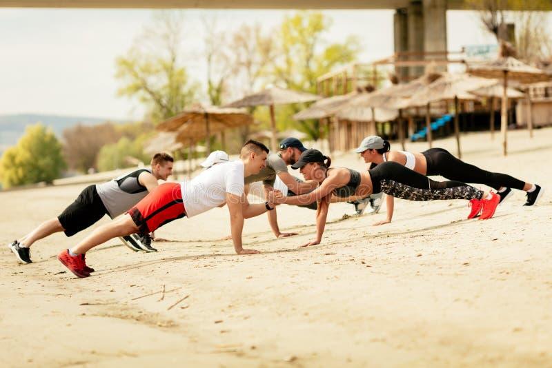Amici del gruppo che si esercitano sulla spiaggia fotografie stock