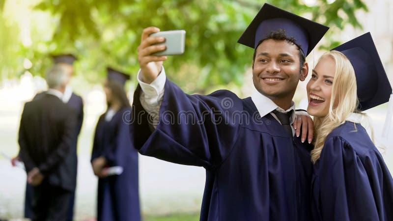 Amici dell'istituto universitario in regalia accademica che prende foto con il cellulare e che la controlla immagini stock