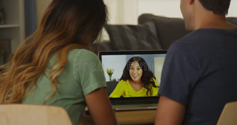 Amici della corsa mista che parlano online sul computer portatile fotografia stock