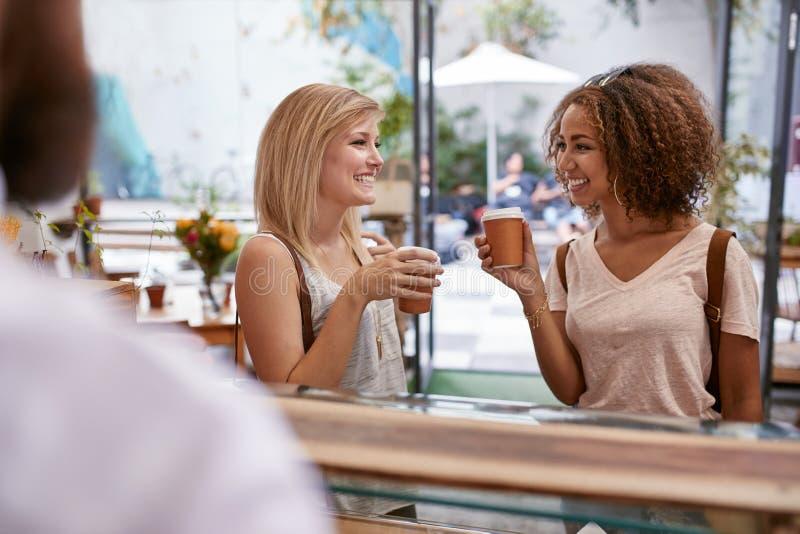 Amici delle giovani donne che ordinano in una caffetteria fotografia stock