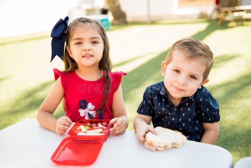 Amici di asilo che mangiano insieme pranzo fotografia stock