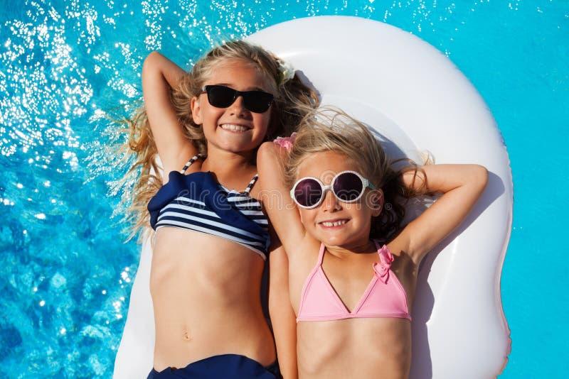 Amici di ragazze che godono dell'estate nella piscina immagini stock