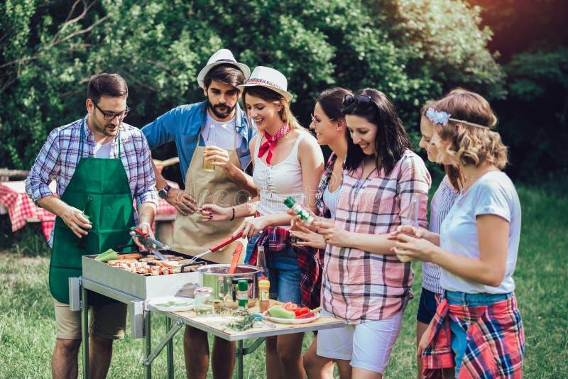 Amici divertendosi grigliando carne che gode del partito del barbecue fotografia stock libera da diritti