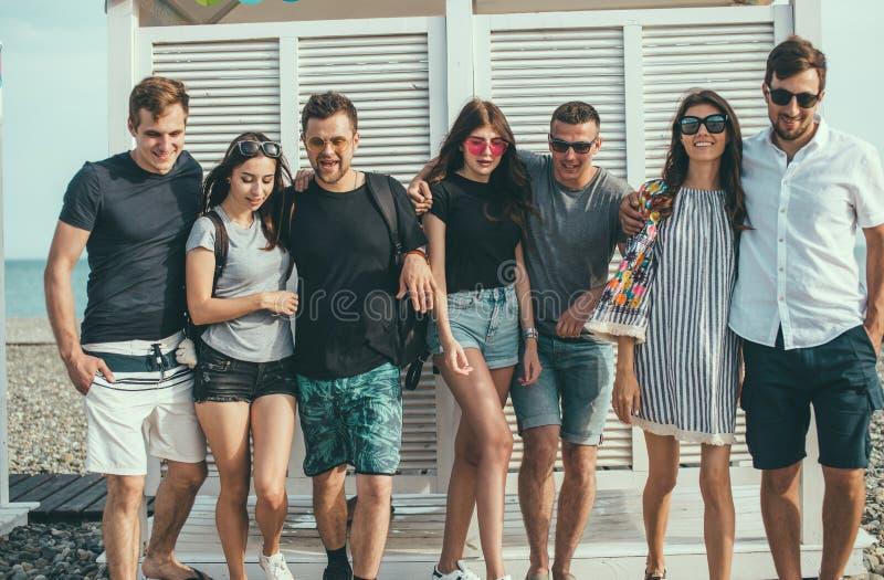 Amici divertendosi insieme sulla vacanza della spiaggia, guardante macchina fotografica fotografie stock libere da diritti