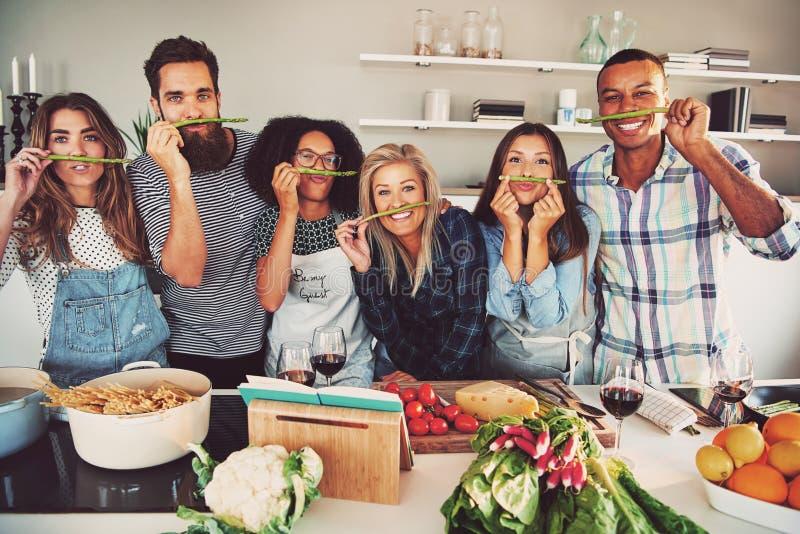 Amici divertenti che fanno i baffi falsi dell'asparago fotografia stock libera da diritti