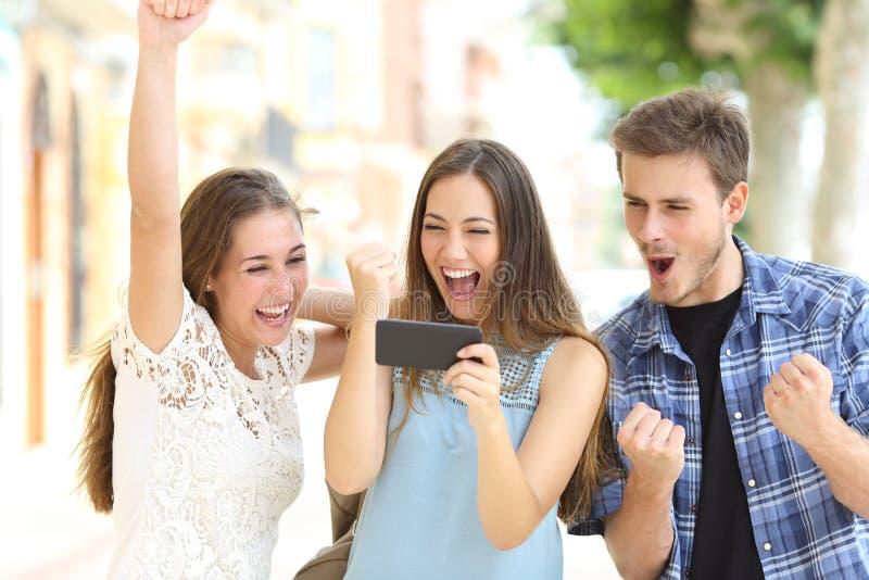 Amici emozionanti che guardano media dallo smartphone immagine stock libera da diritti