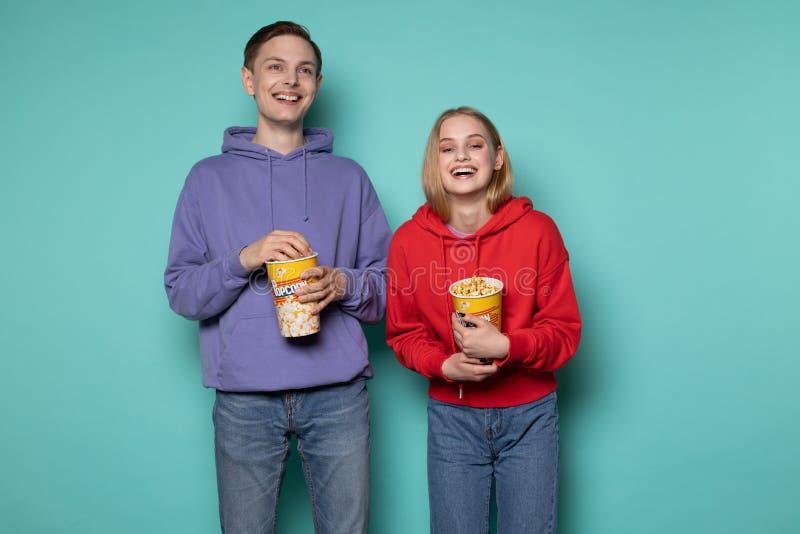 Amici felici, bella ragazza bionda e tipo in maglia con cappuccio porpora guardanti un film della commedia con popcorn in mani fotografia stock
