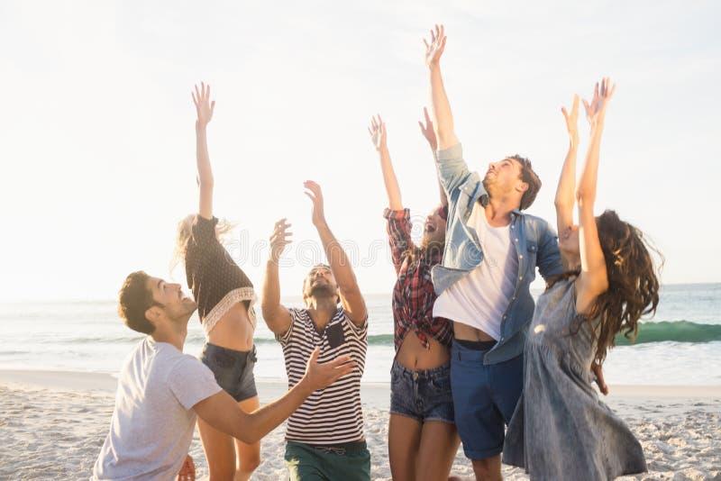 Amici felici che giocano beach volley immagini stock
