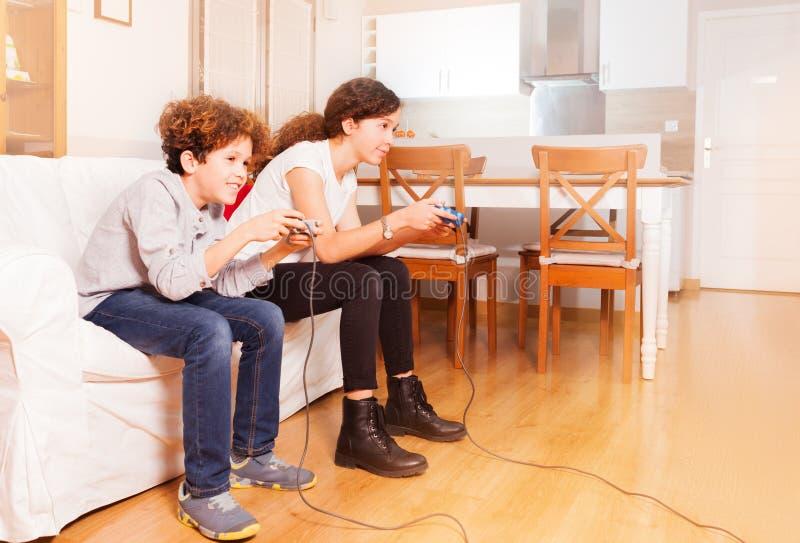 Amici felici che giocano i video giochi a casa fotografia stock libera da diritti