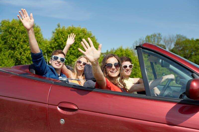 Amici felici che guidano in automobile del cabriolet al paese fotografie stock libere da diritti