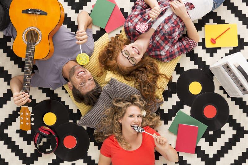 Amici felici che mangiano le lecca-lecca surronded dai vinili immagine stock