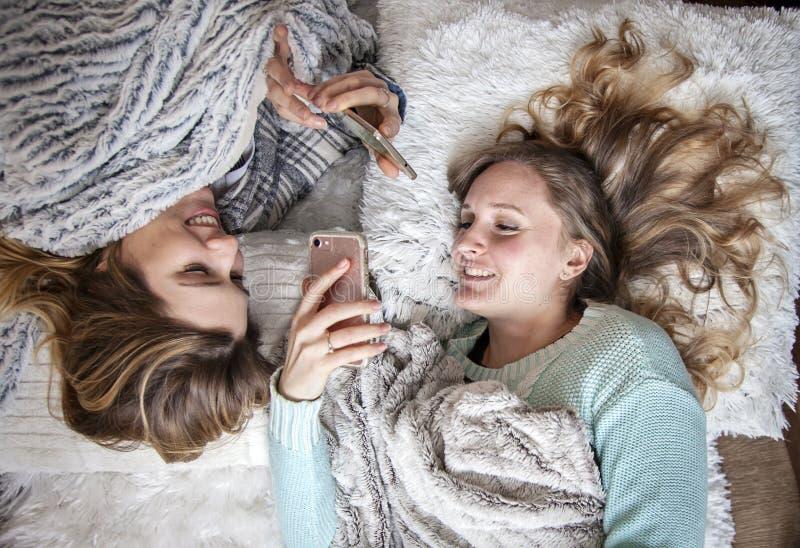 Amici felici che mettono sulle coperte con la risata dei telefoni immagini stock libere da diritti