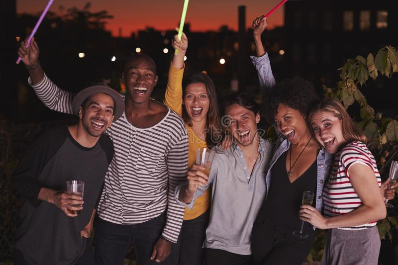 Amici felici che ondeggiano i glowsticks al partito del tetto a Brooklyn immagini stock libere da diritti