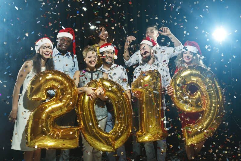 Amici felici che tengono un simbolo di 2019 anni al partito fotografie stock