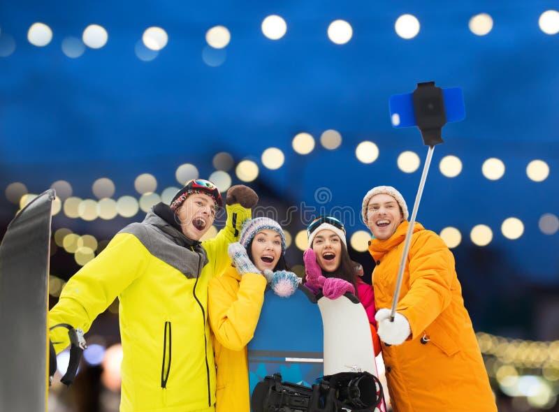 Amici felici con gli snowboard e lo smartphone immagini stock libere da diritti