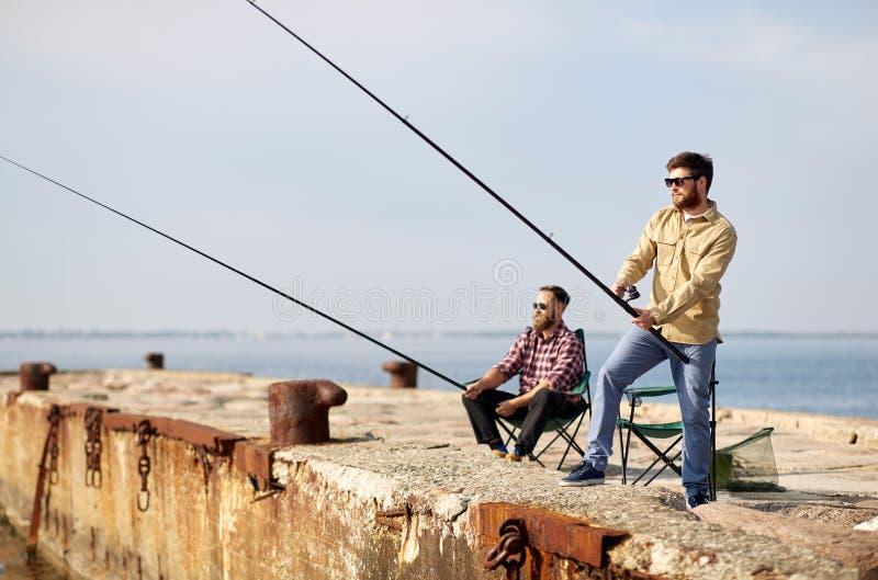 Amici felici con le canne da pesca sul pilastro fotografia stock