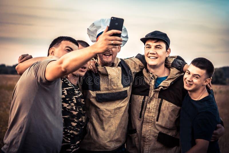 Amici felici degli uomini che rendono a concetto di fotografia del selfie del gruppo forte stile di vita maschio di amicizia fotografia stock