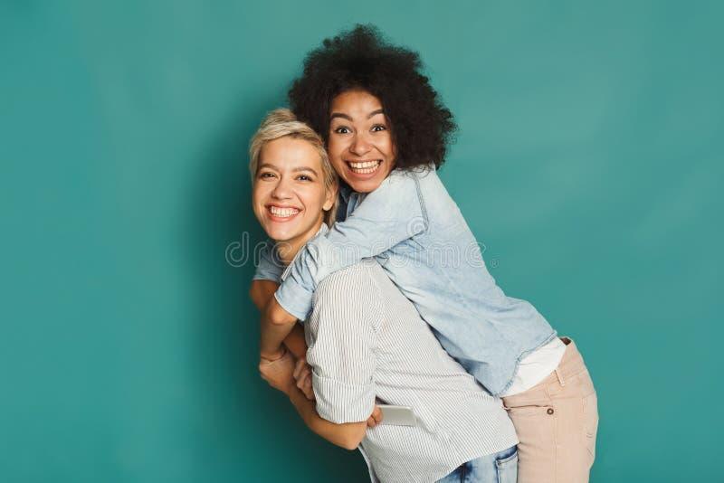 Amici felici divertendosi al fondo blu fotografia stock
