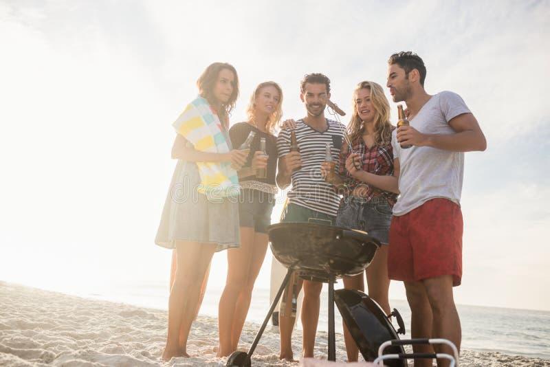 Amici felici divertendosi intorno al barbecue fotografia stock libera da diritti