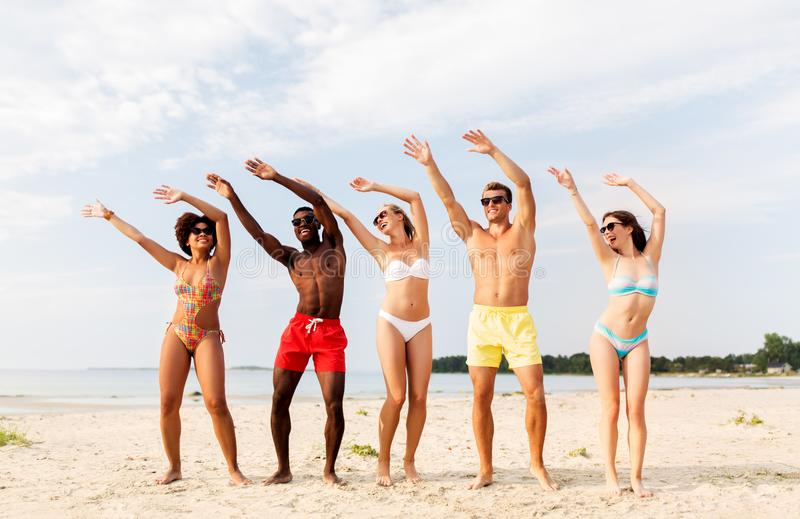 Amici felici divertendosi sulla spiaggia di estate immagini stock