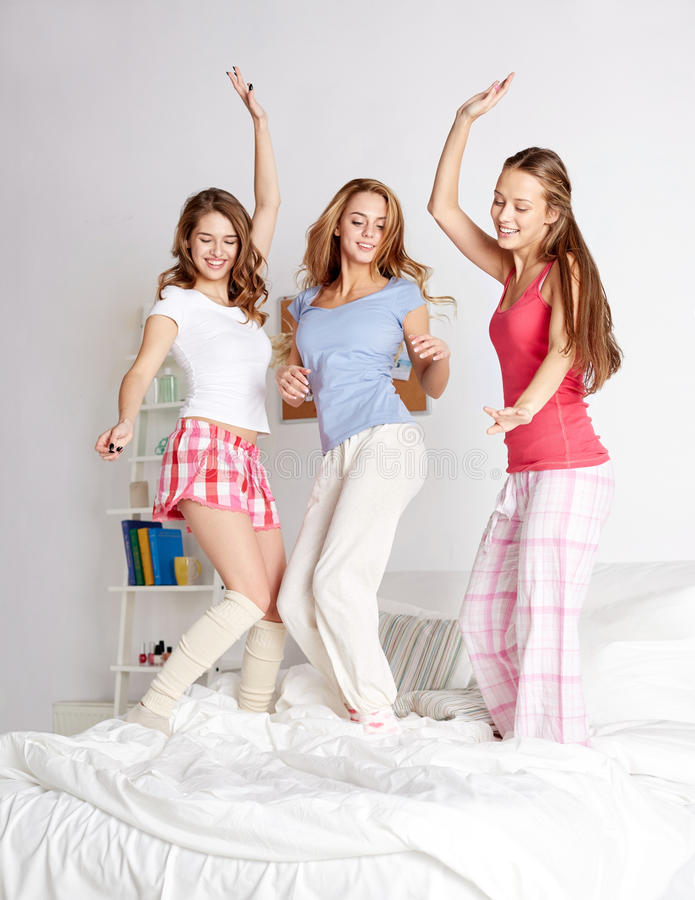 Amici felici o ragazze teenager divertendosi a casa fotografia stock