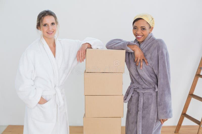Amici femminili in accappatoi dalle scatole in nuova casa fotografia stock libera da diritti