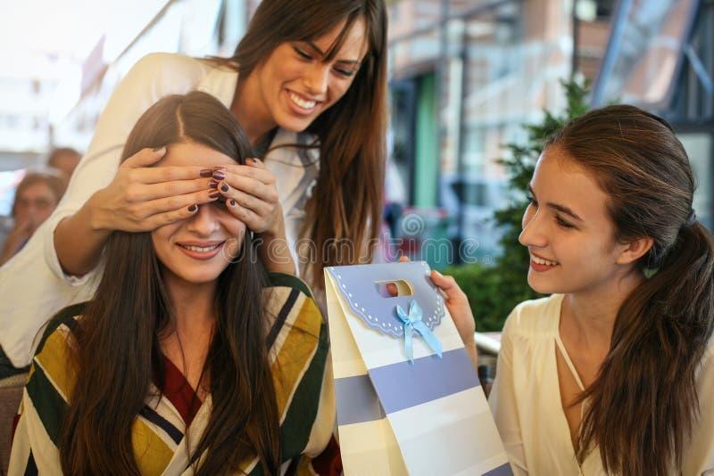 Amici femminili che danno il regalo di compleanno La ragazza ha sorpreso il loro amico immagini stock