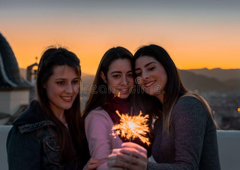 Amici femminili con le stelle filante all'aperto al tramonto immagine stock