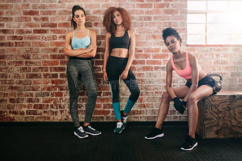 Amici femminili della corsa mista in palestra fotografie stock